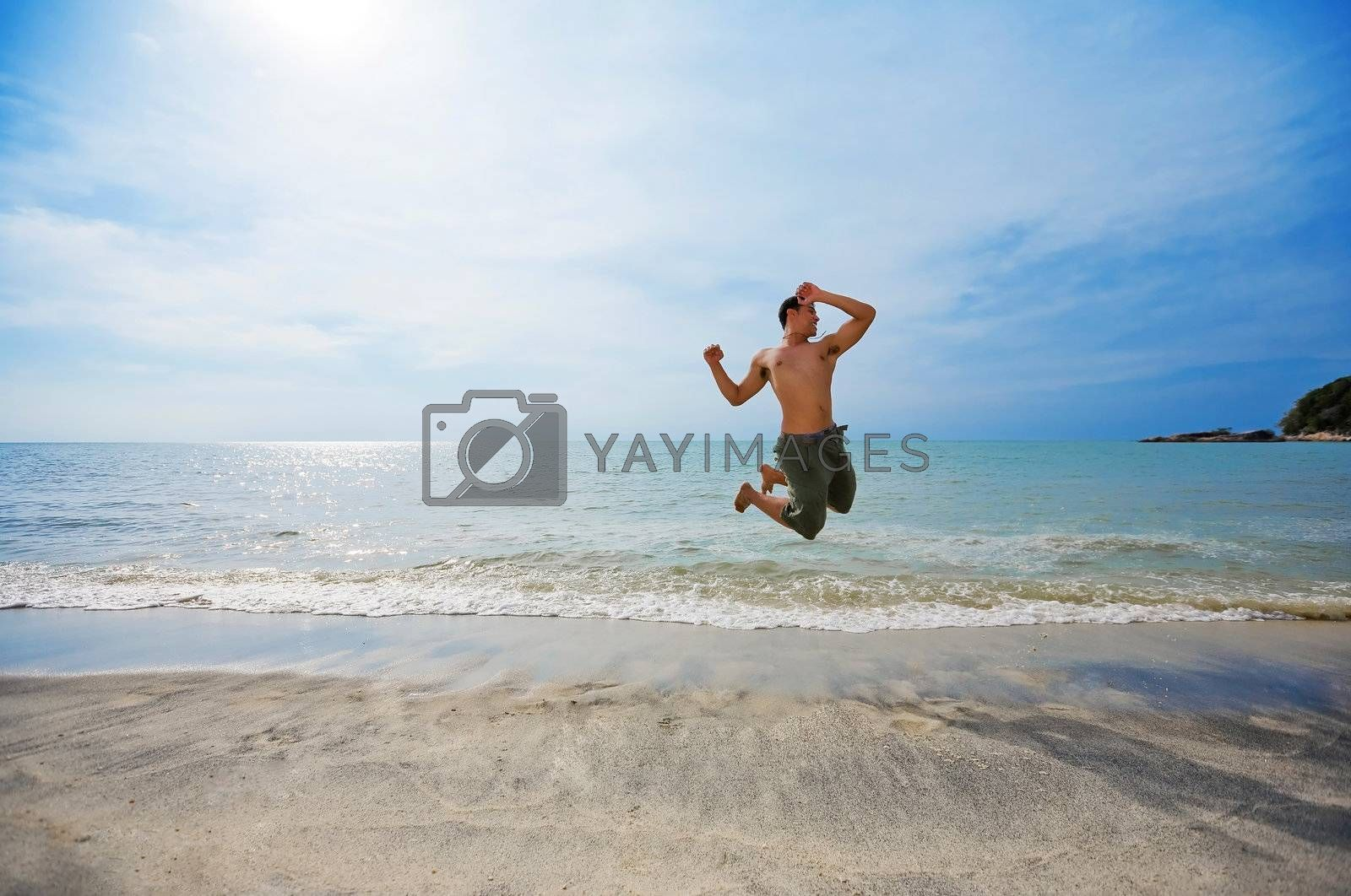 happy man jumping excitedly by the beach