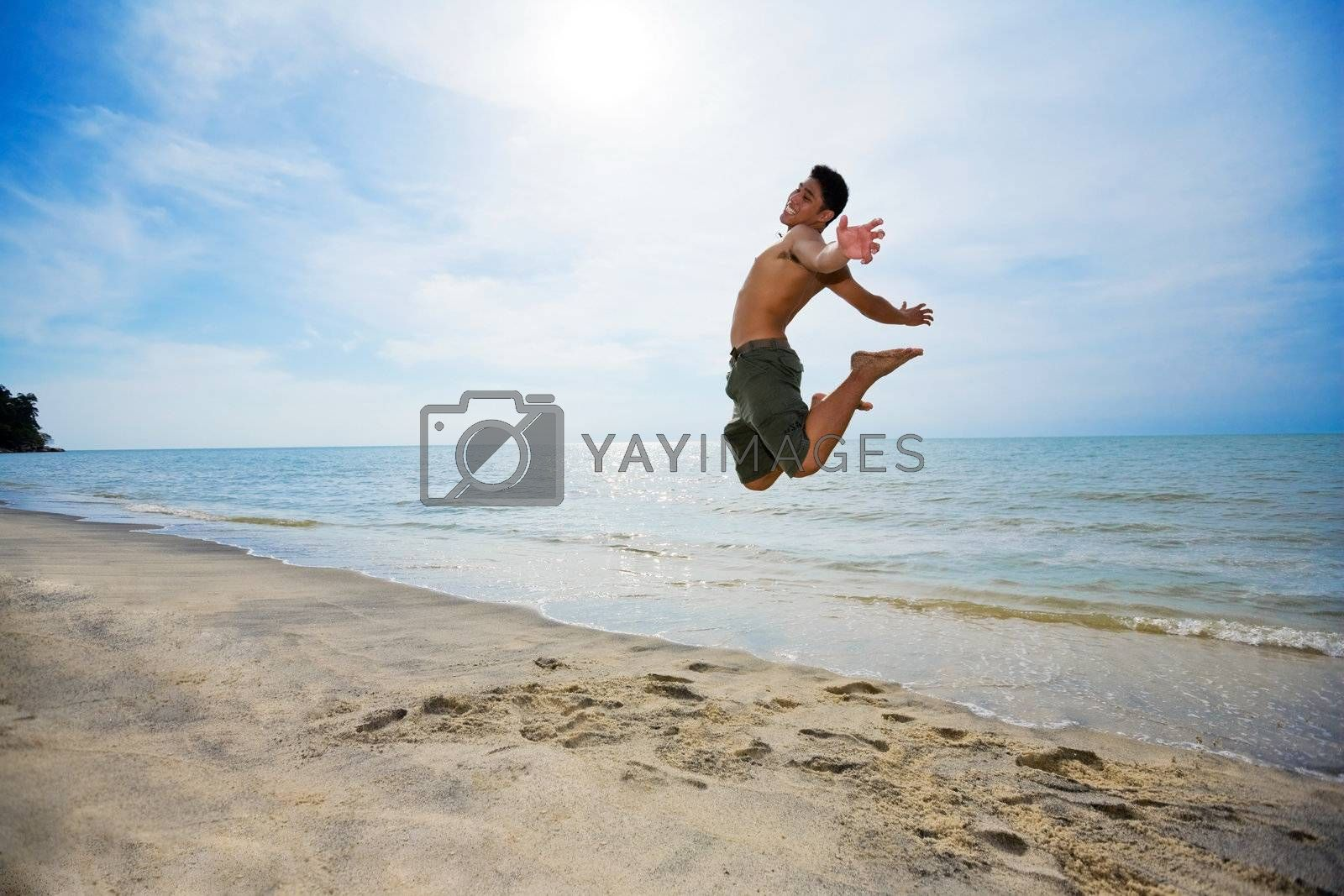 happy man jumping up high by the beach in a beautiful day