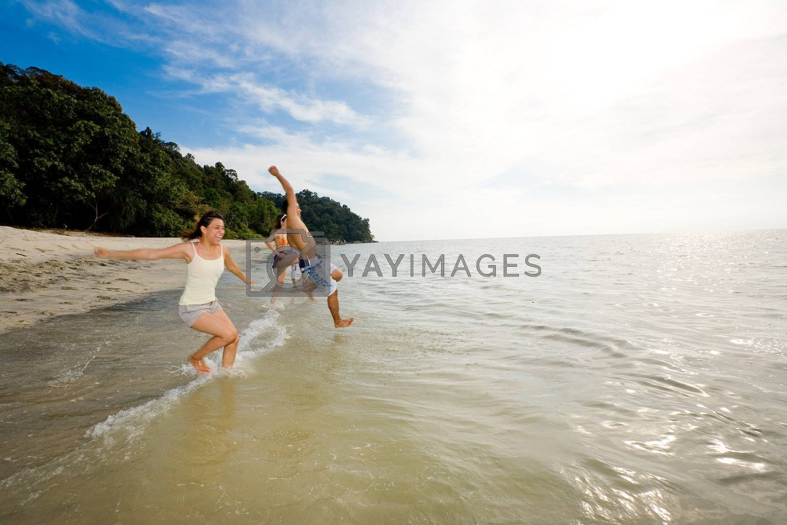 a group of friends having fun by the beach jump into the sea