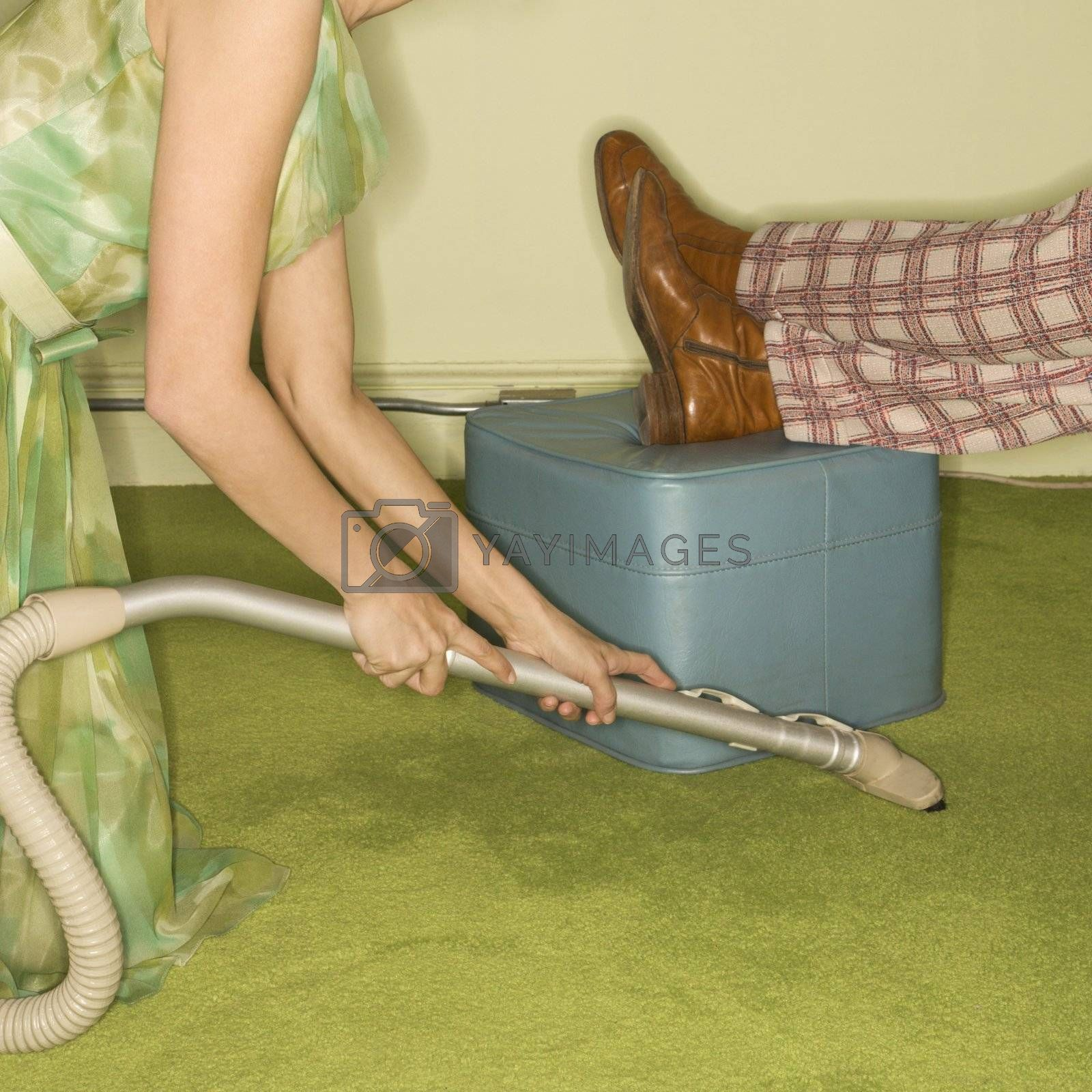 Caucasian mid-adult woman kneeling and vaccuuming carpet around male feet resting on foot stool.