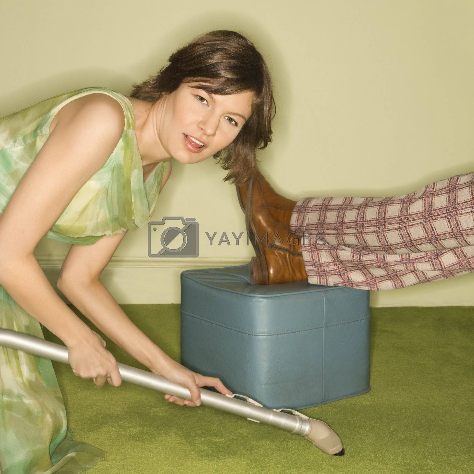 Unhappy pretty Caucasian mid-adult woman kneeling and vaccuuming carpet around male feet resting on foot stool.