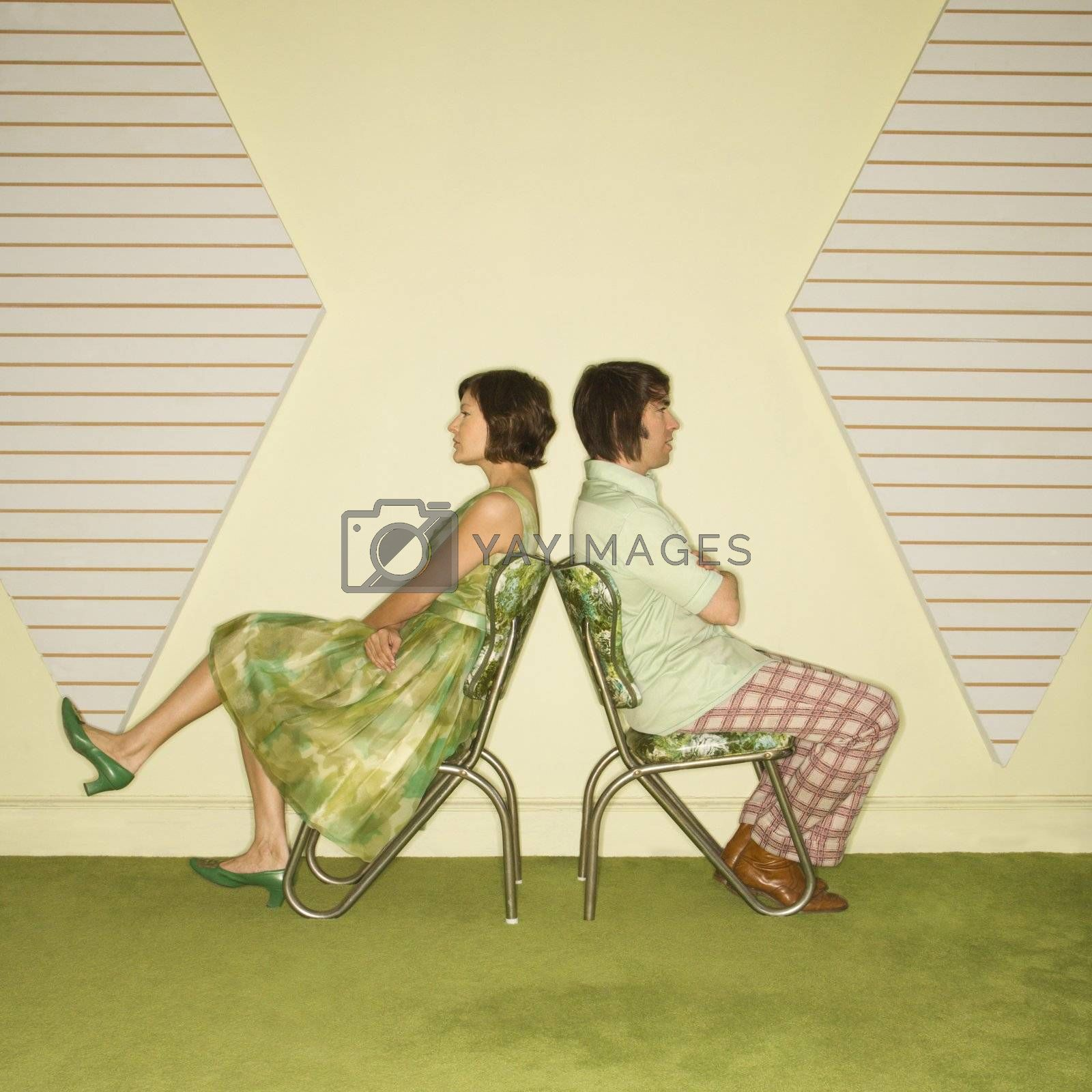Caucasian mid-adult couple wearing vintage clothing sitting back to back in green vinyl chairs with arms crossed.