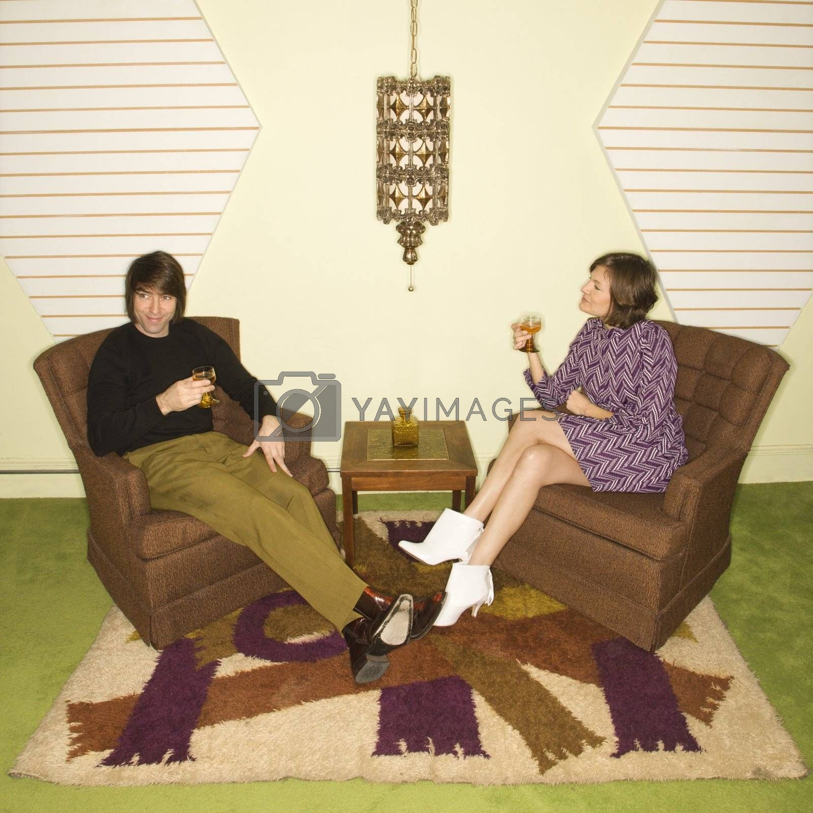Caucasian mid-adult man and woman wearing vintage clothing seated in brown retro chairs smiling and drinking.