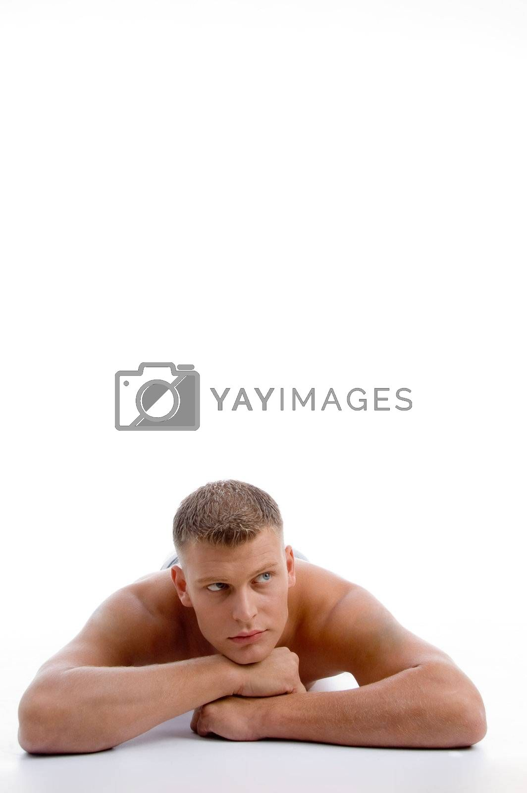laying muscular male looking aside on an isolated background
