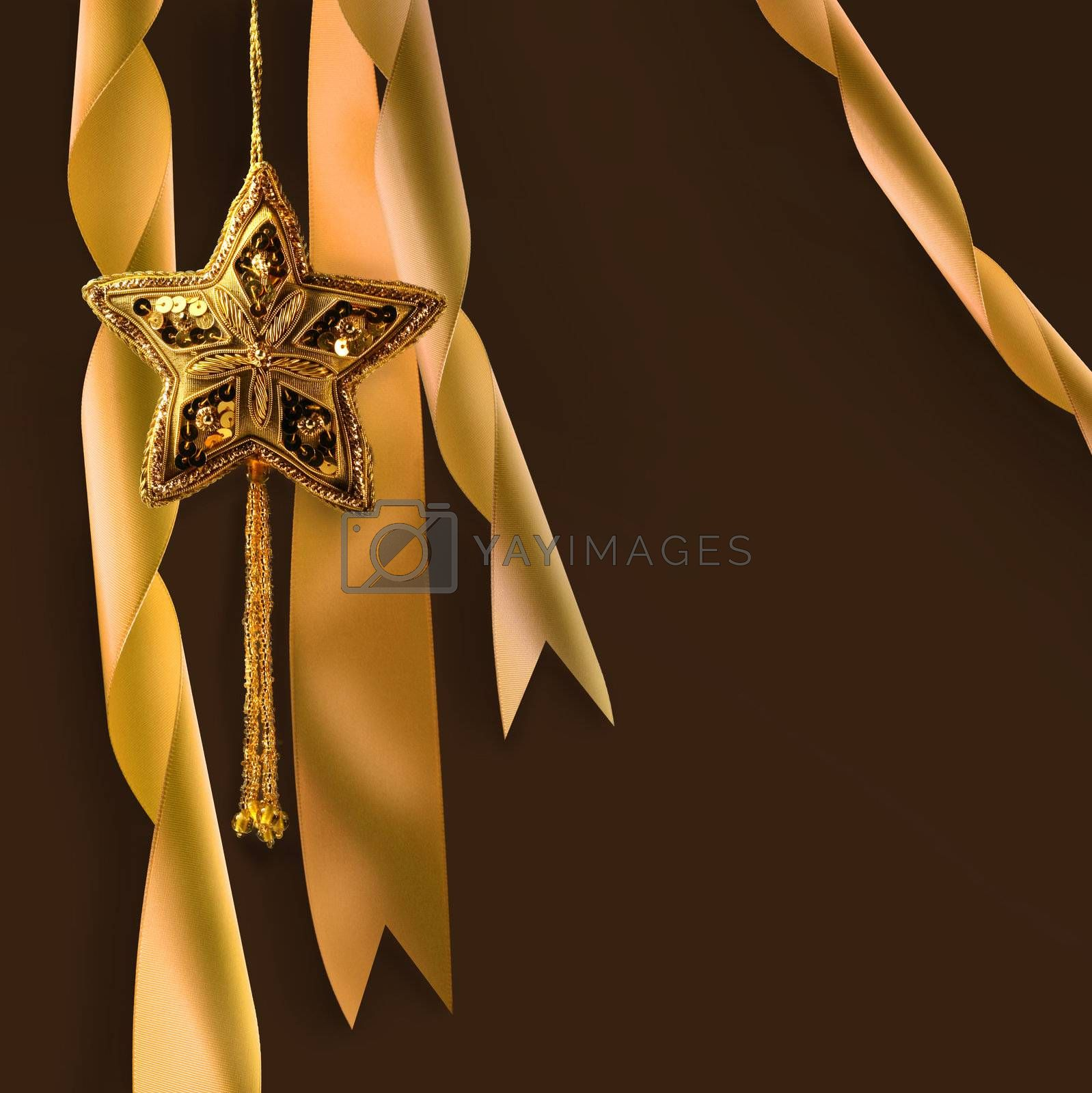 Gold christmas star with ribbons against dark background