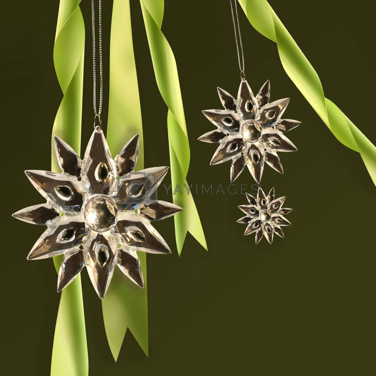 Crystal snowflakes with green ribbons on dark background