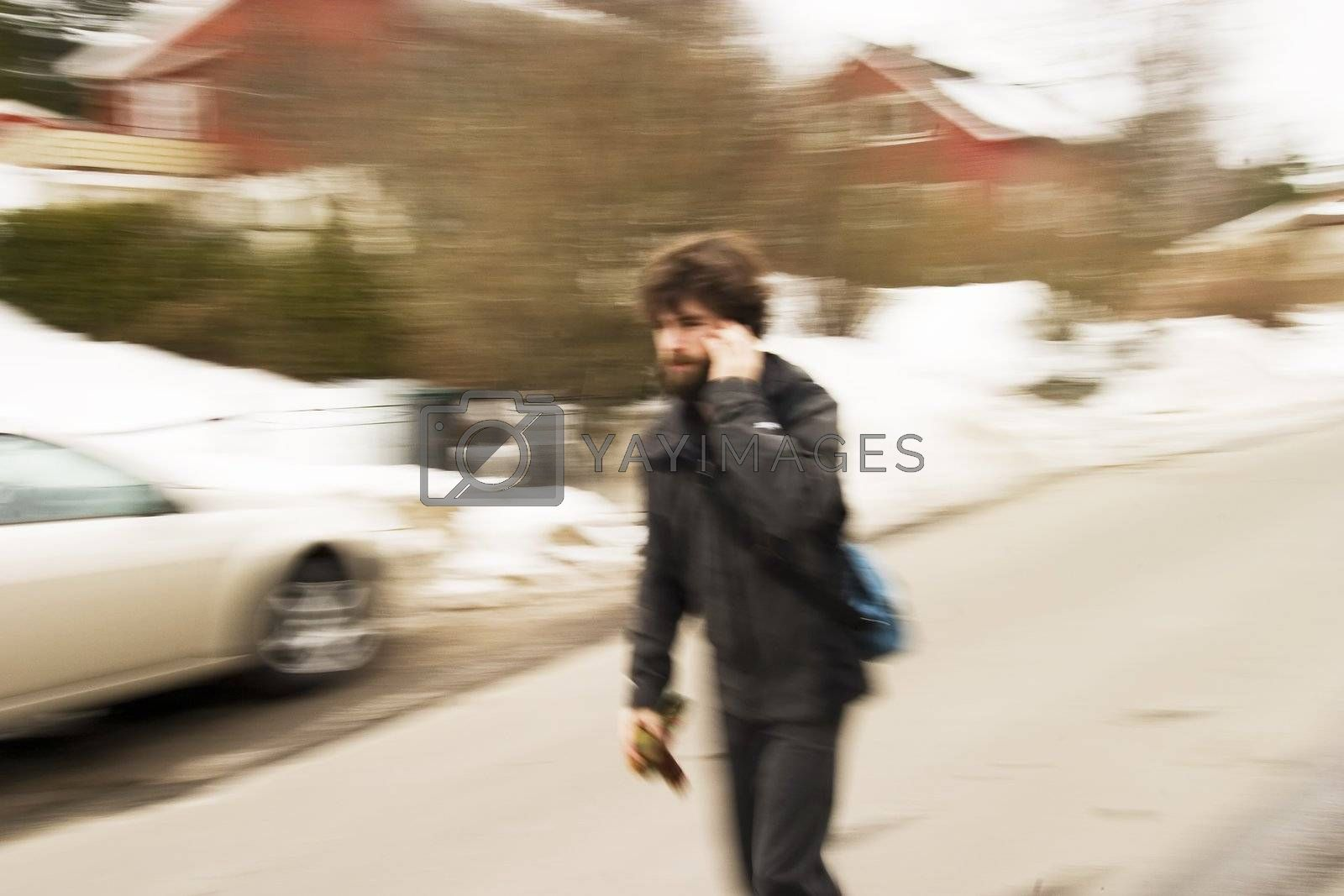 A motion blur abstract of a person walking in a hurry talking on a cell phone, a late rushing concept image.