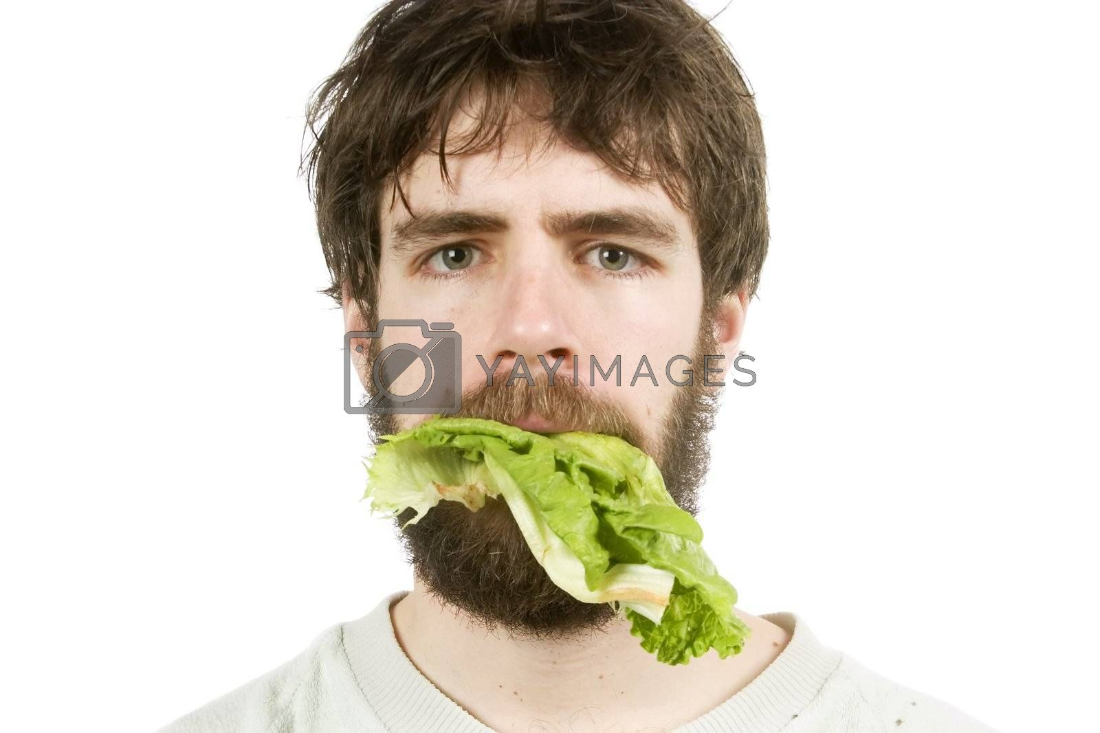 A young male with lettuce in his mouth, looking unimpressed.