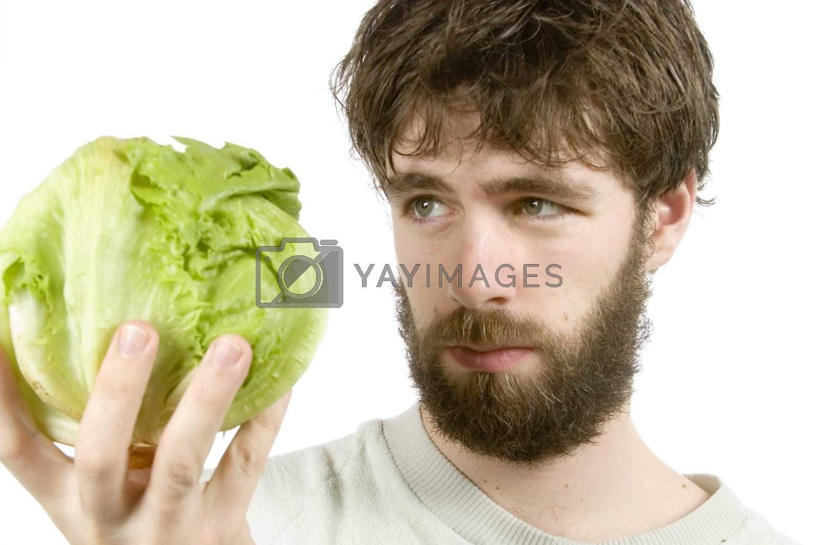 A young male with a beard looking at salad with scepticism.  The salad is out of focus.