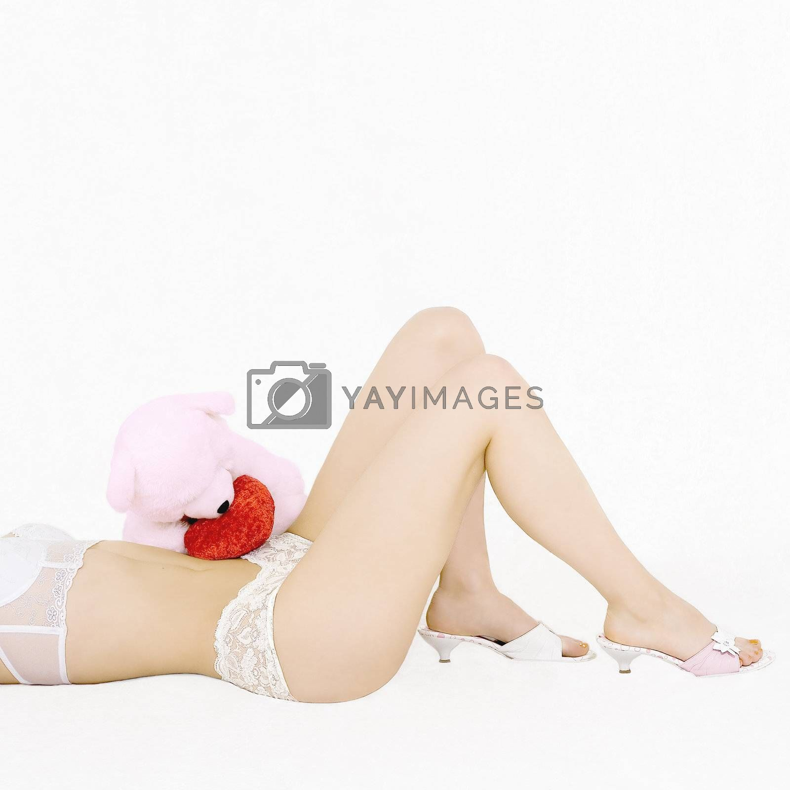 Woman legs and plush bear with a heart