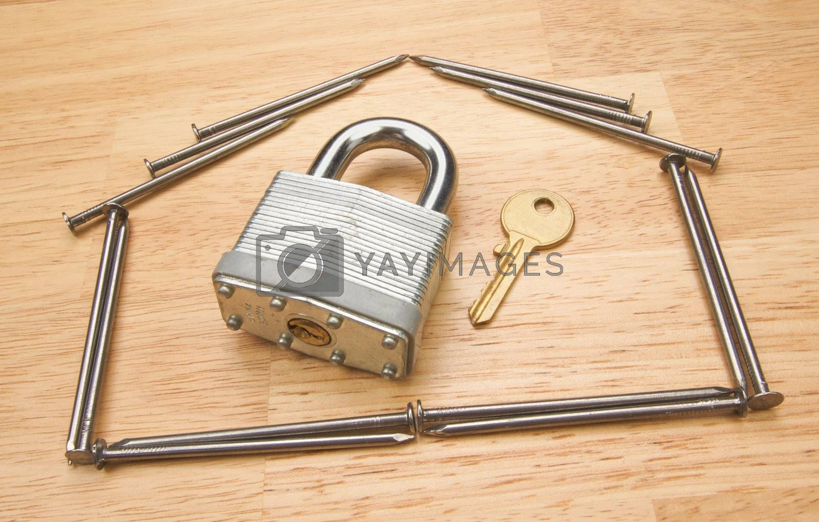 House of Nails with Lock and Key on a Wood Background.
