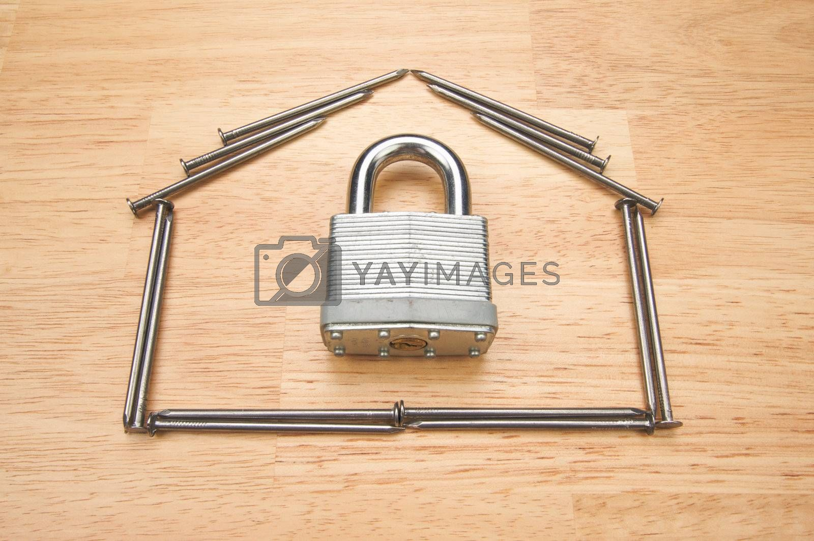House of Nails with Lock on a Wood Background.