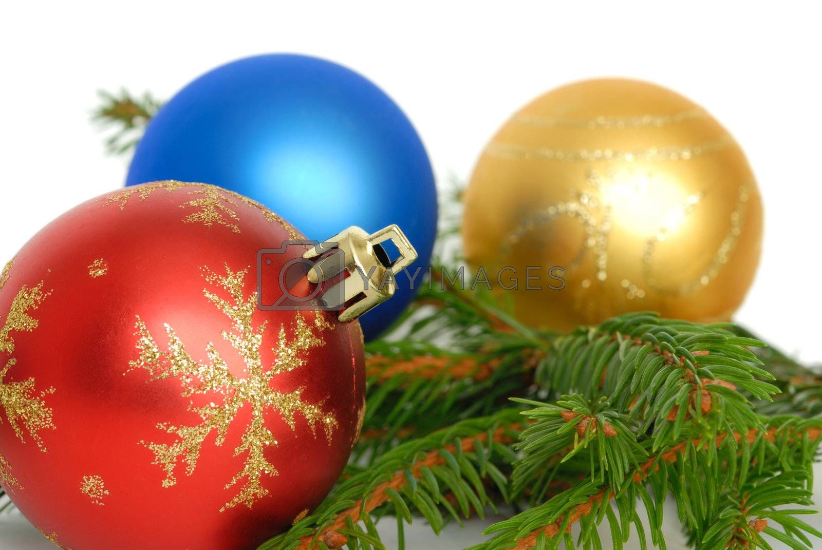Christmas baubles and green branch on white background