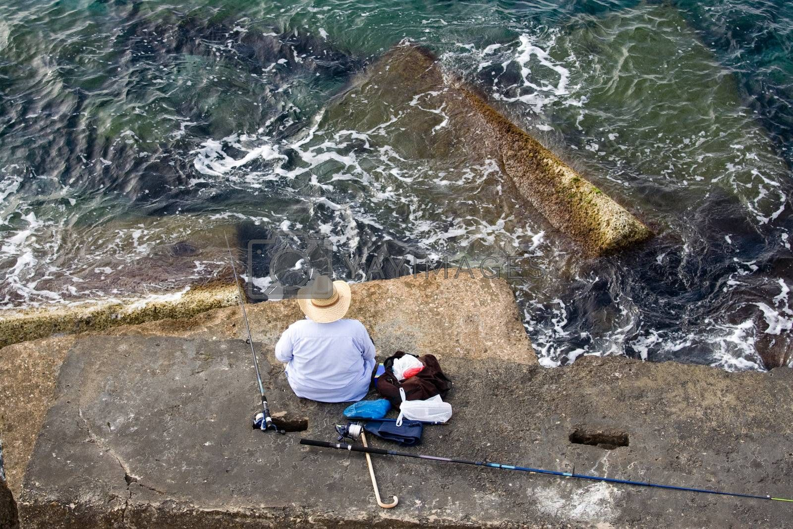 Fisherman in hat is sitting on the stone and fishing, top horizontal view