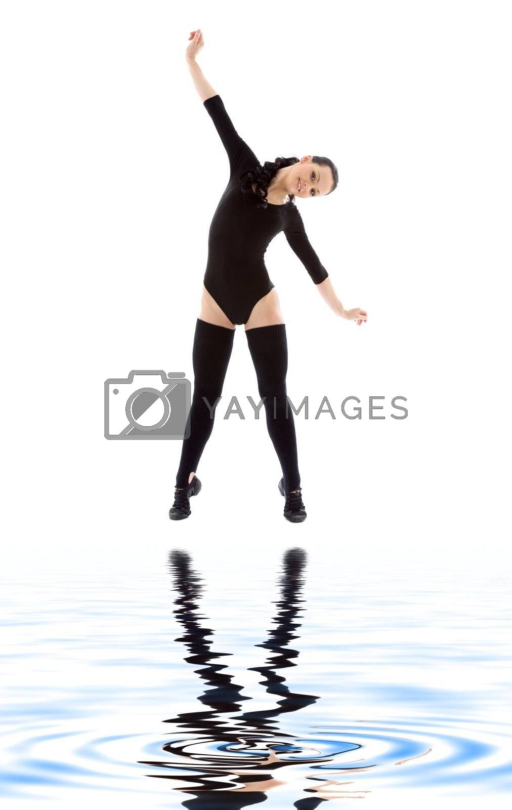 lovely girl in black leotard working out on white sand