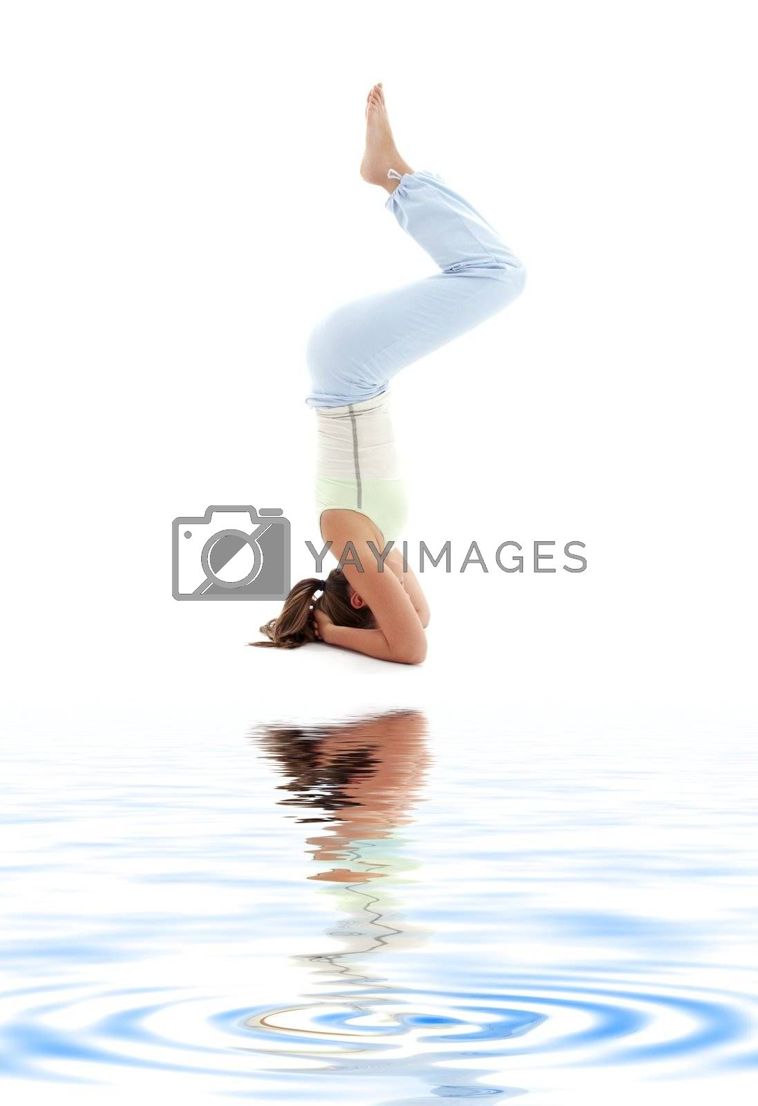 sporty girl practicing salamba sirsasana supported headstand on white sand
