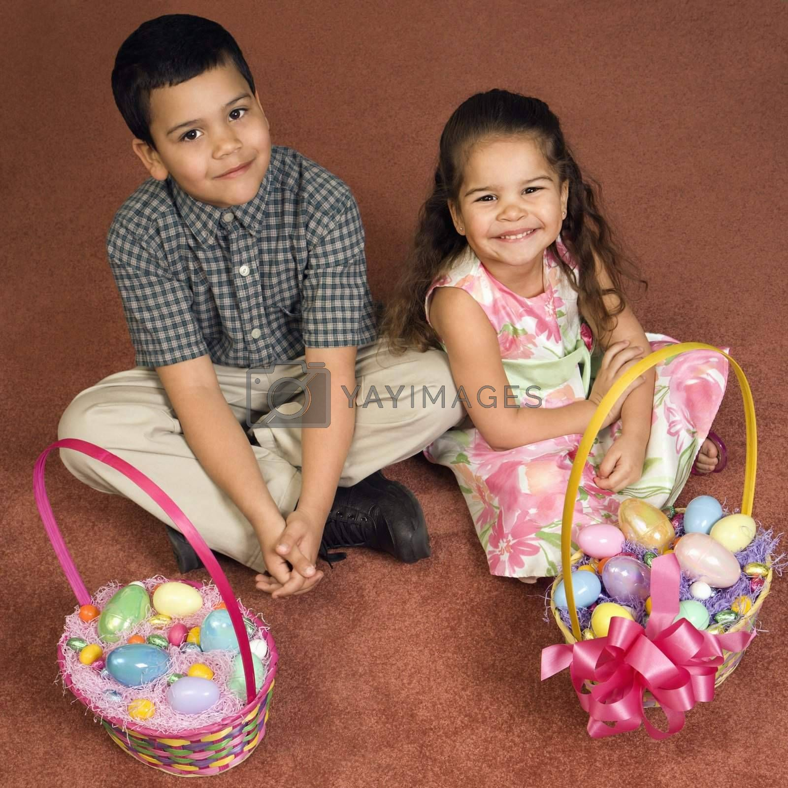 Hispanic brother and sister sitting on floor with Easter baskets looking up at viewer smiling.