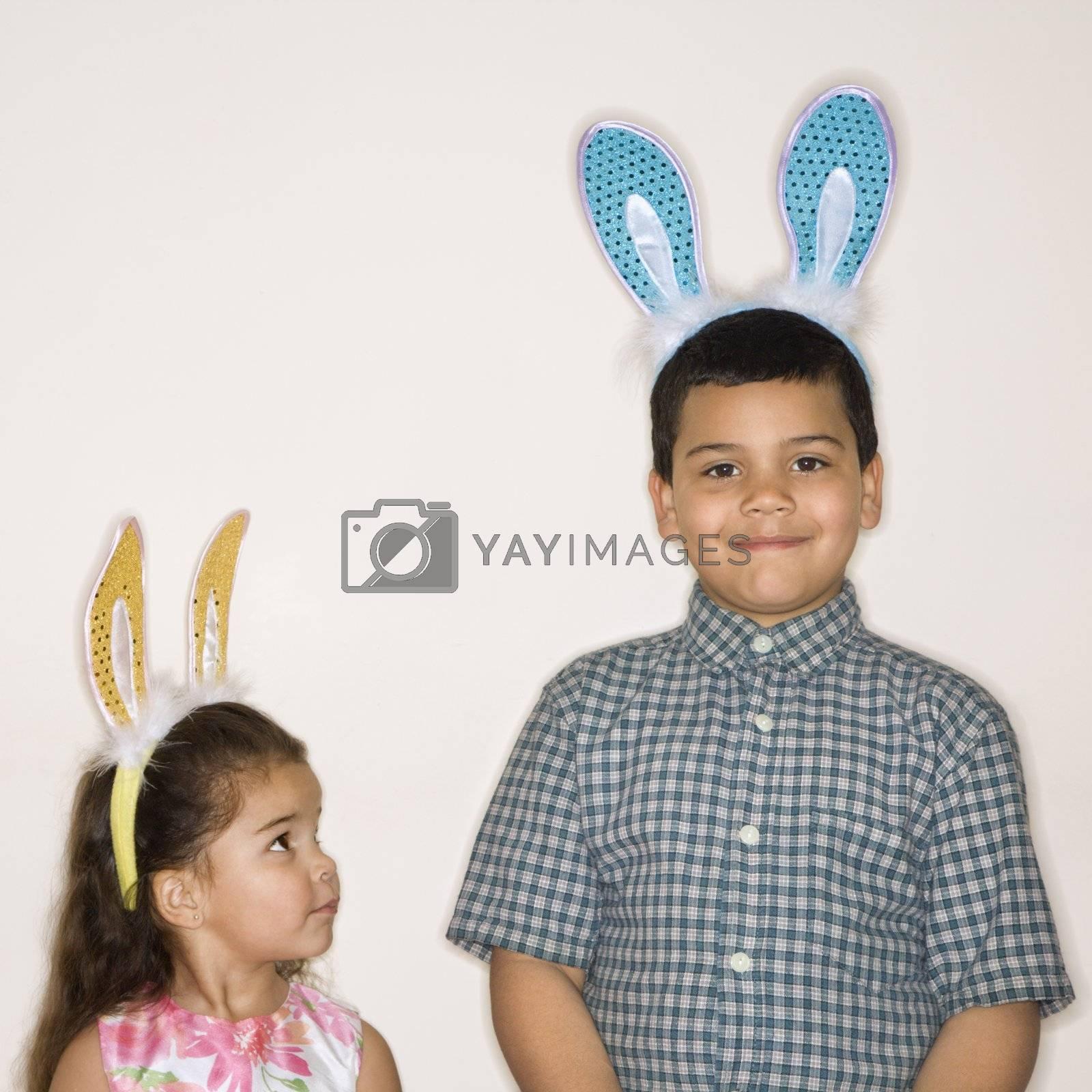 Hispanic girl looking up at Hispanic boy both wearing bunny ears.