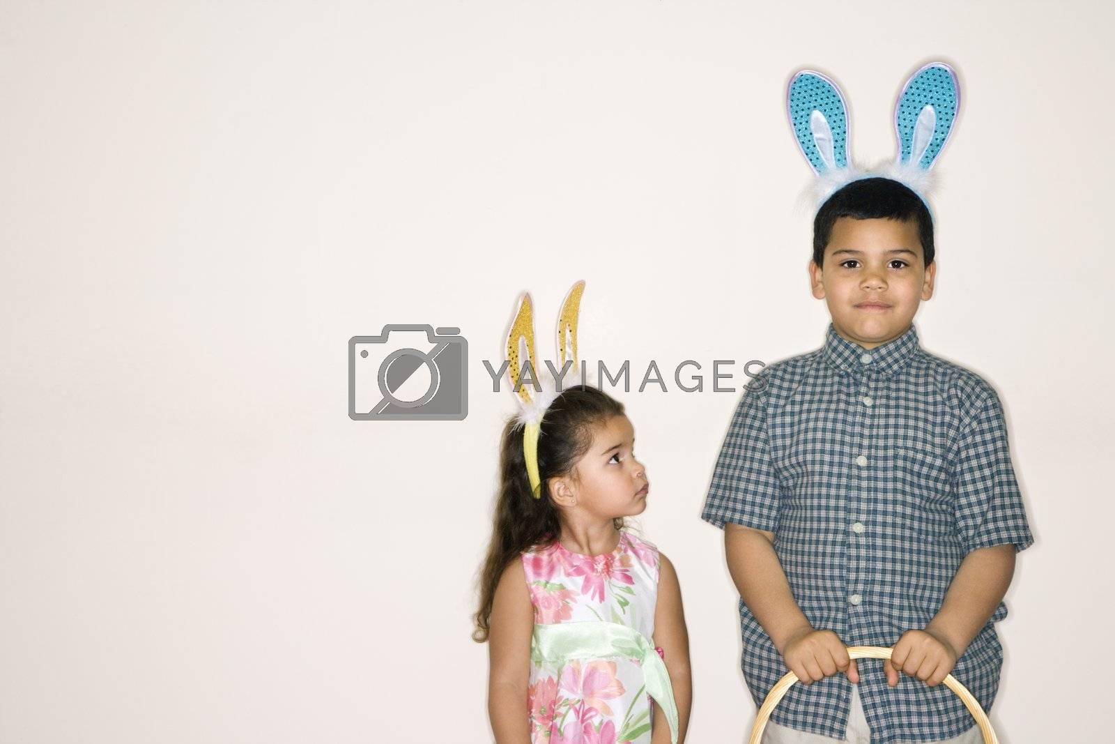 Hispanic girl looking up at Hispanic boy holding Easter basket both wearing bunny ears.
