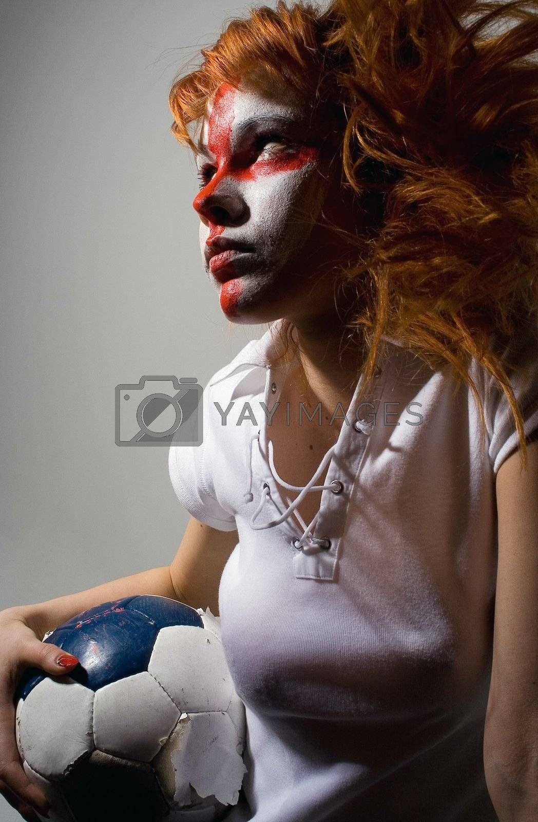english football makeup girl holding worn soccer ball, looking forward