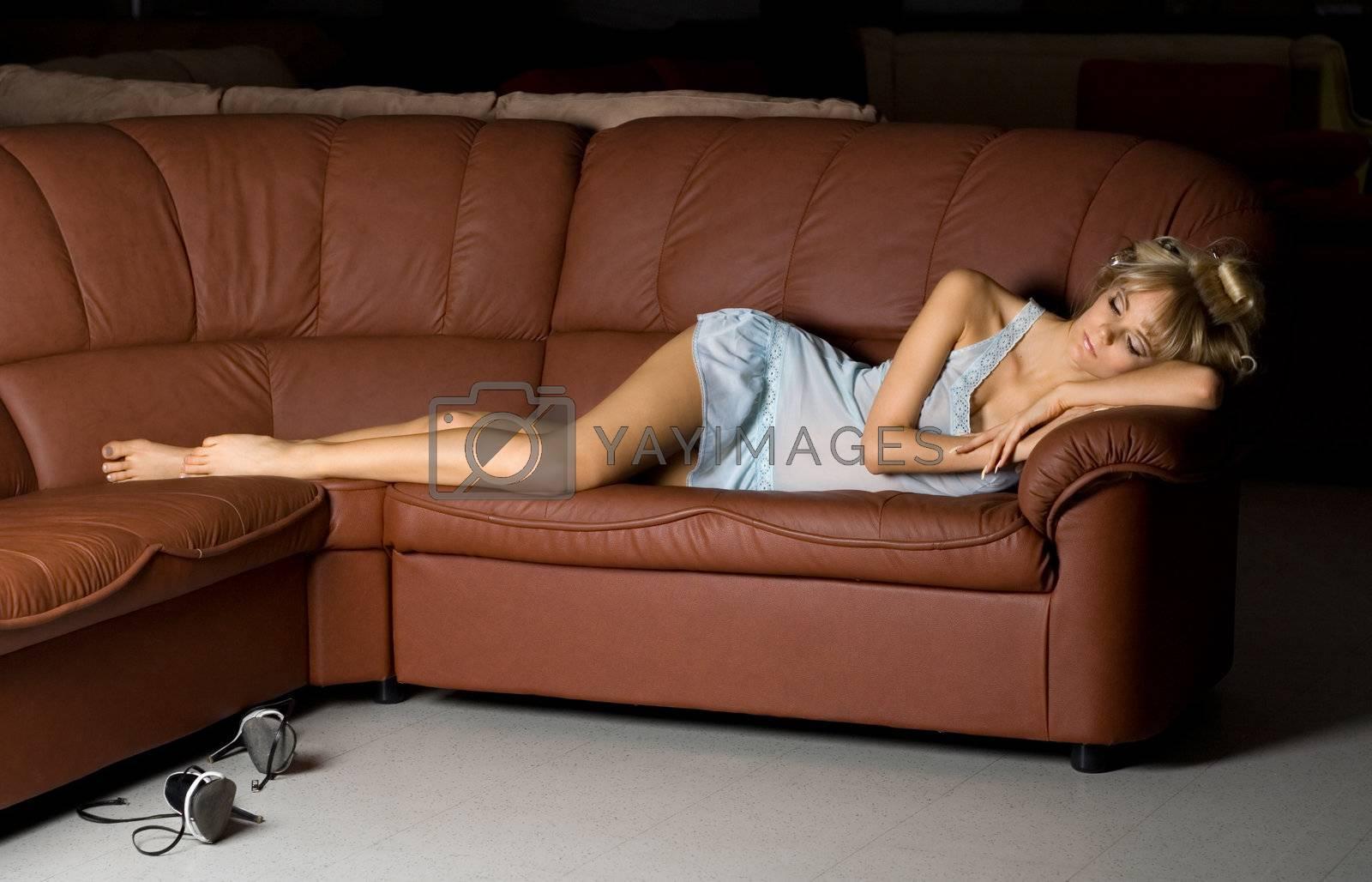 beautiful girl in blue lingerie sleeping on the sofa