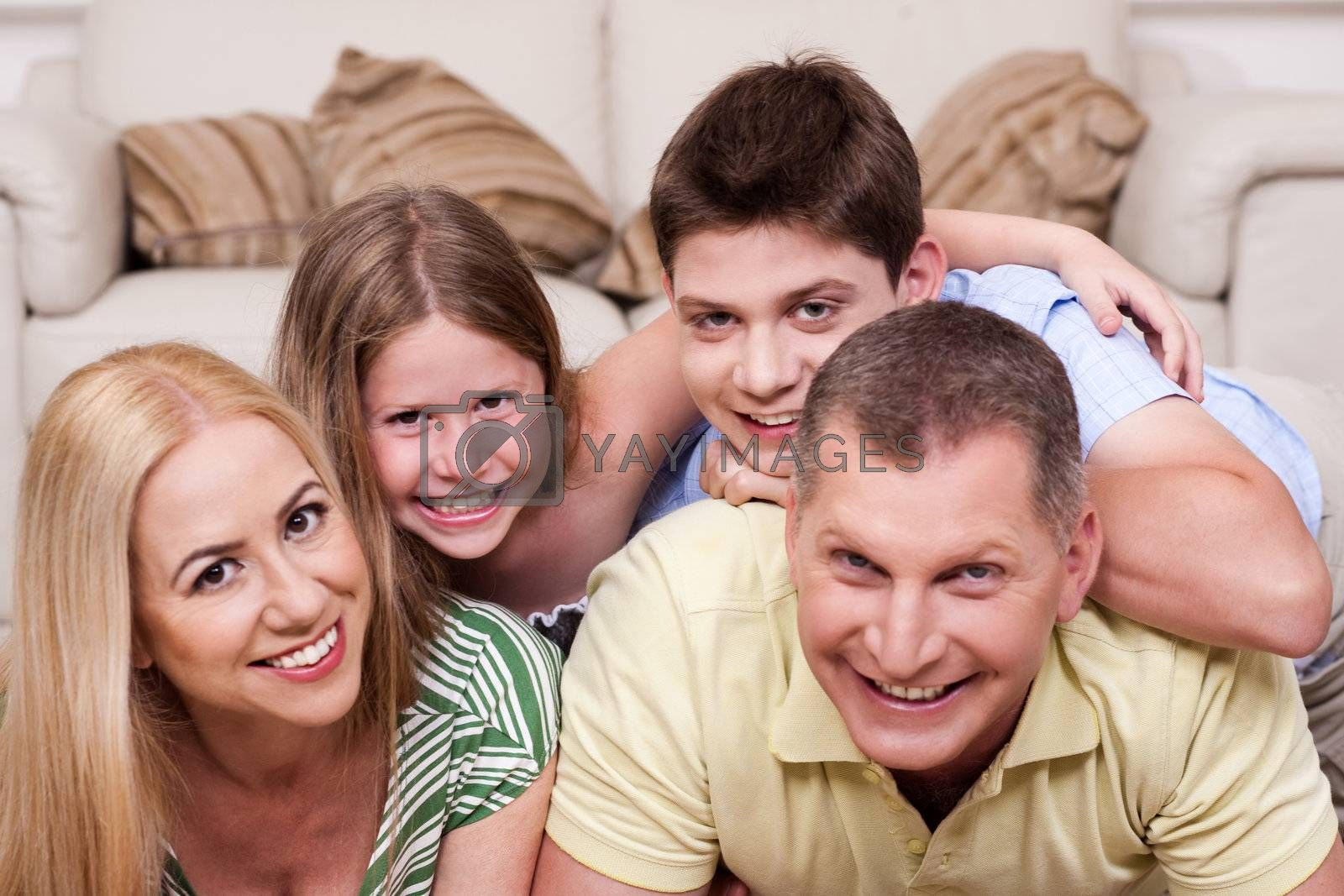 Smiling family lying together on the floor in living room