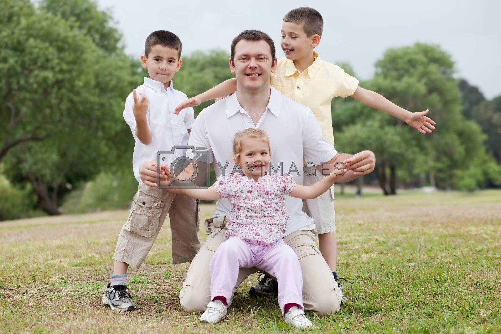 Happy family posing together on natural background looking at you