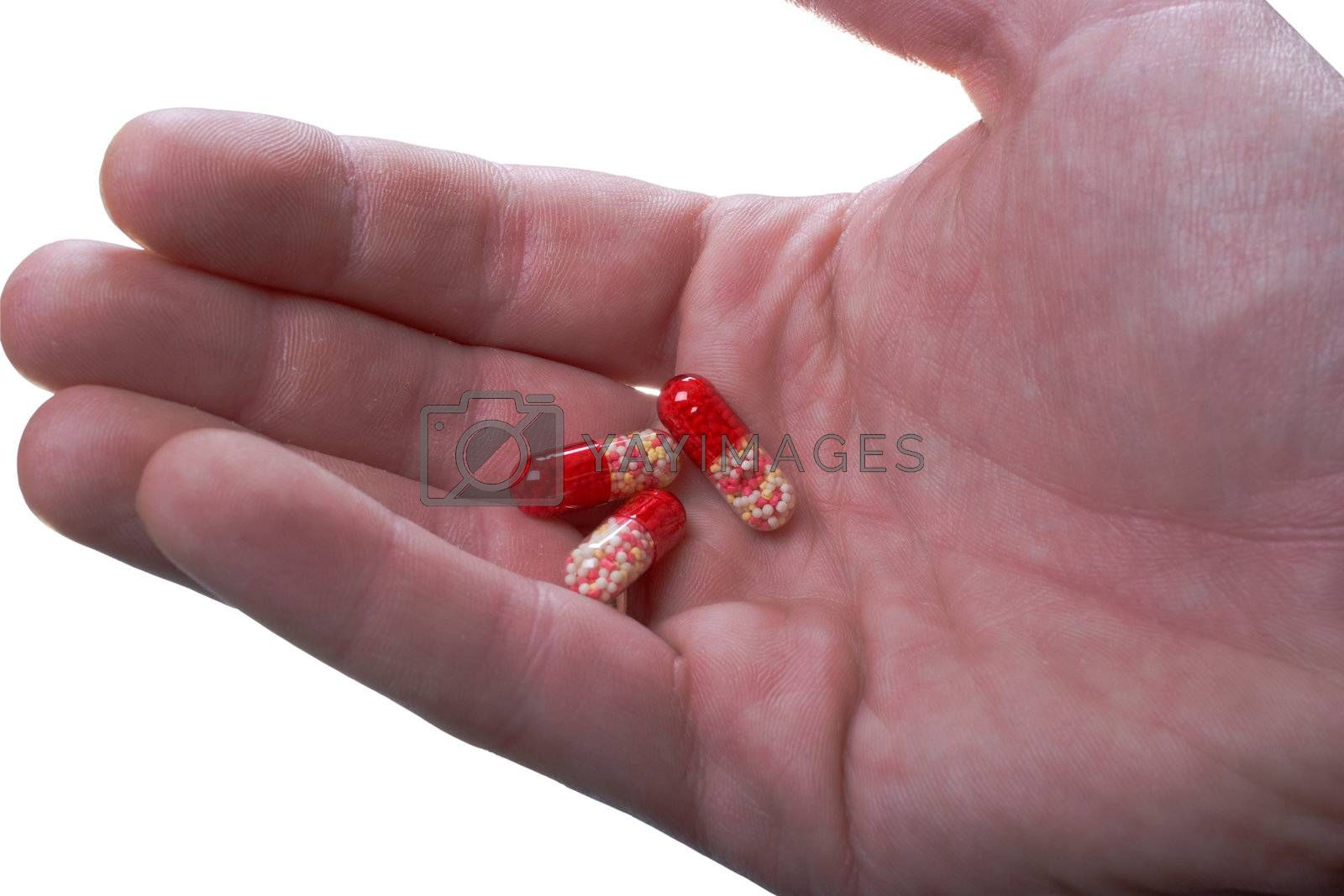 Multi-coloured capsules on a palm. It is isolated, on a white background