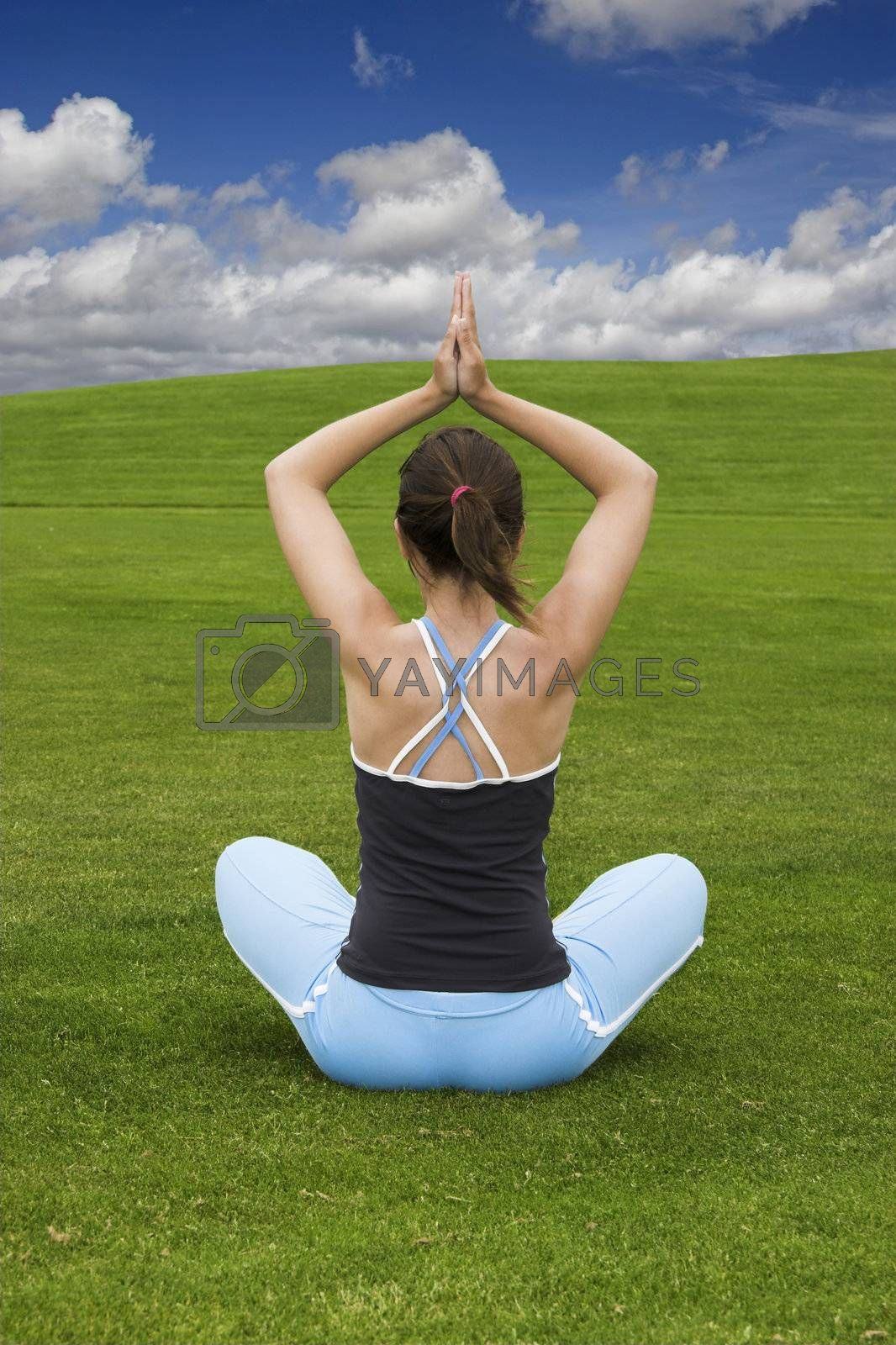 Athletic woman making yoga on a green meadow