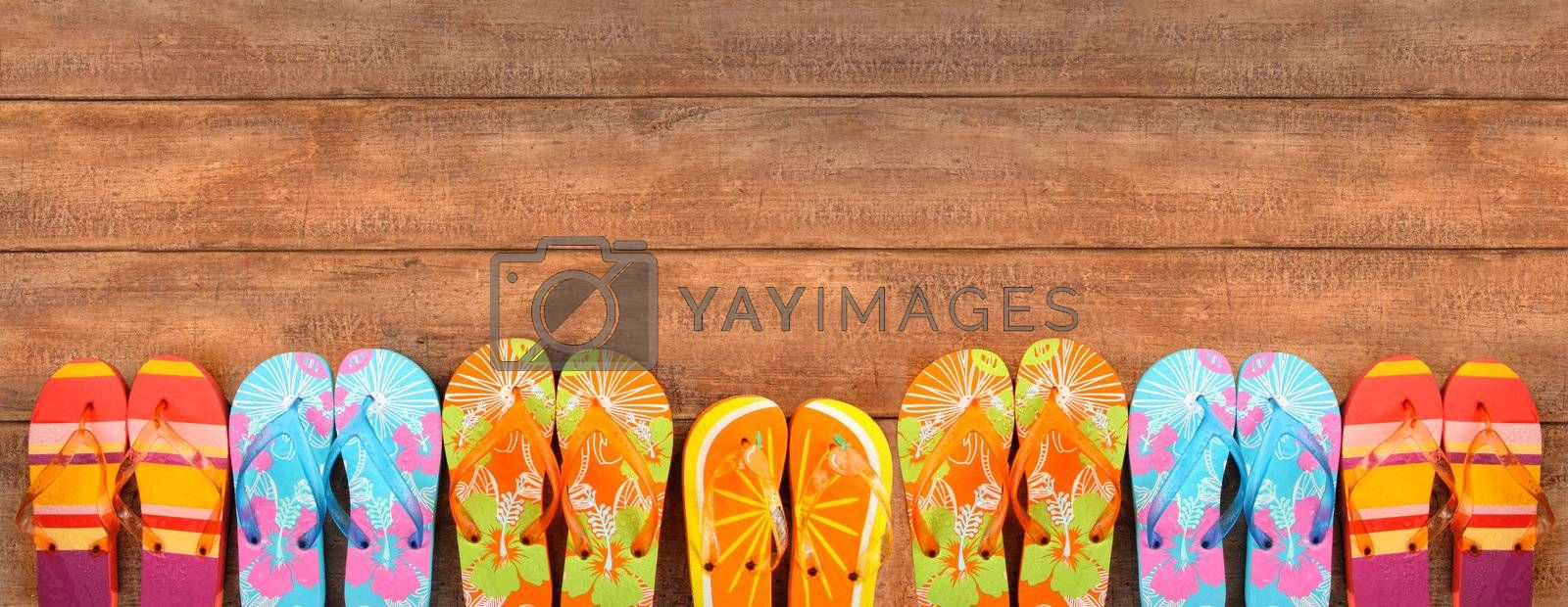 Brightly colored flip-flops on wood deck