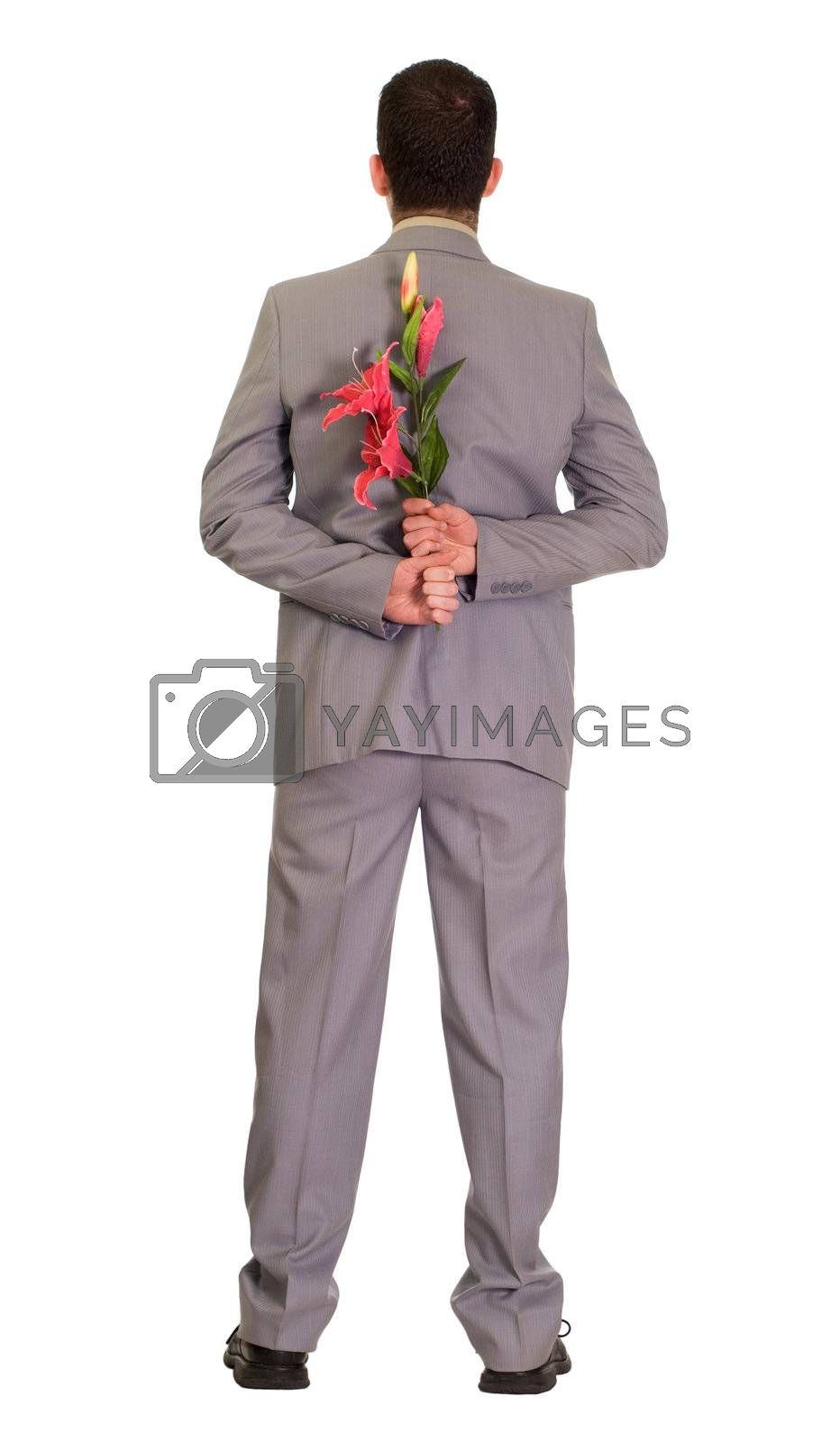 Full body view of a man wearing a suit holding some fake flowers behind his back