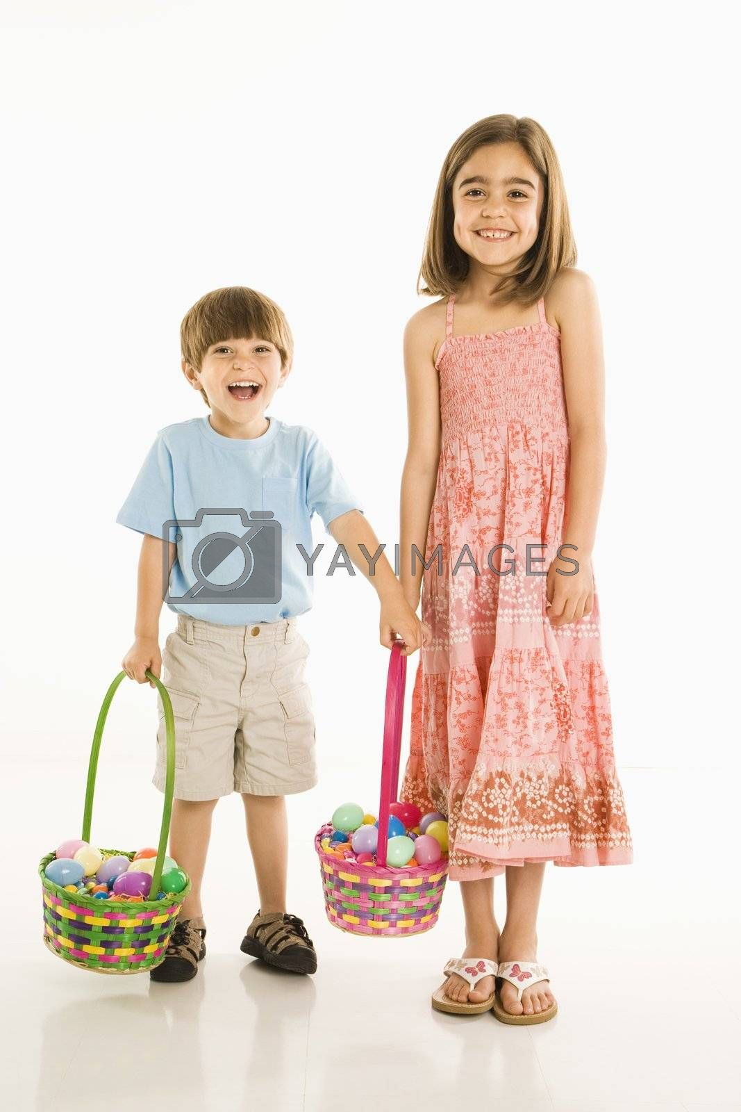 Smiling girl and boy standing with Easter baskets against white background.