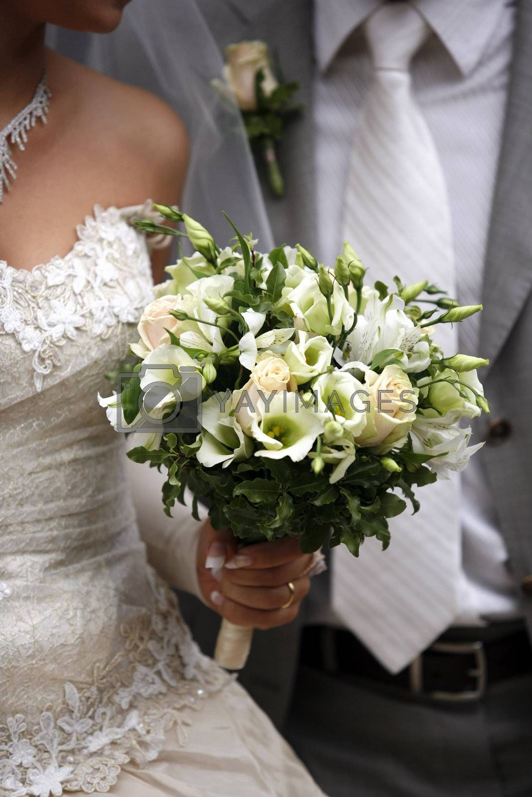 Bouquet of flowers on a background of a dress of the bride and a suit the groom.