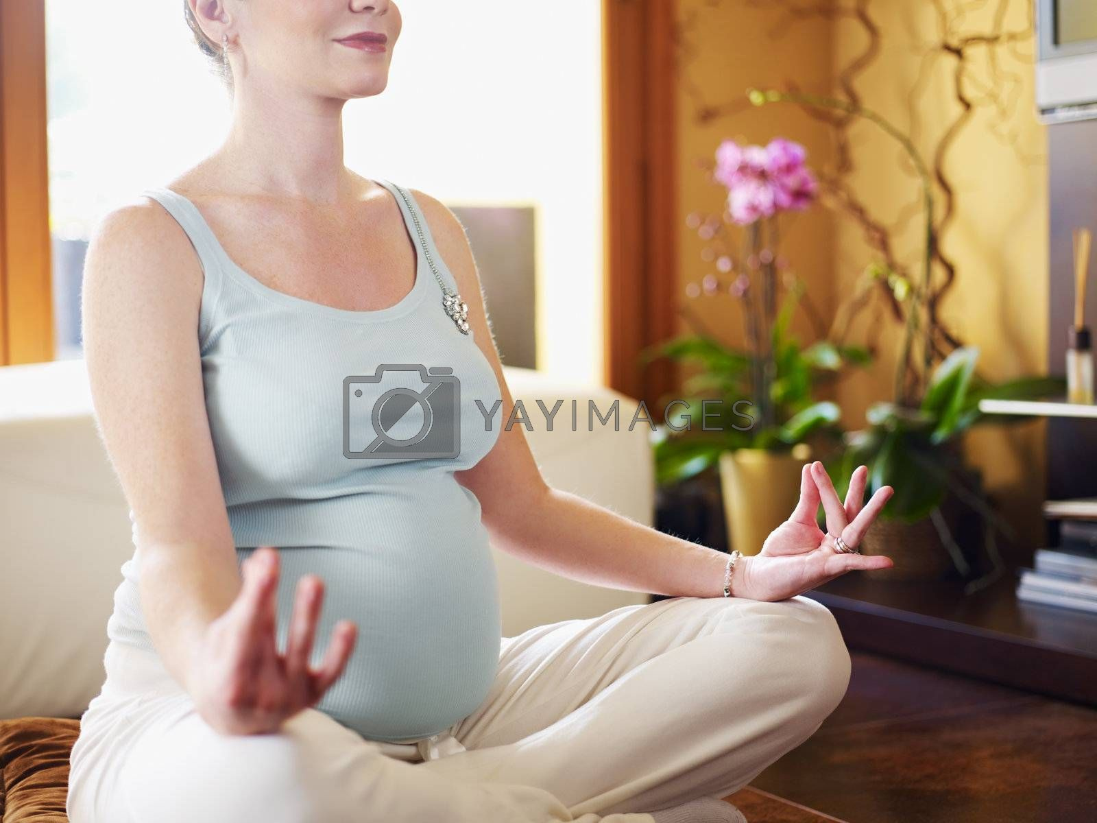 cropped view of italian 6 months pregnant woman sitting with crossed legs doing yoga exercise at home. Horizontal shape