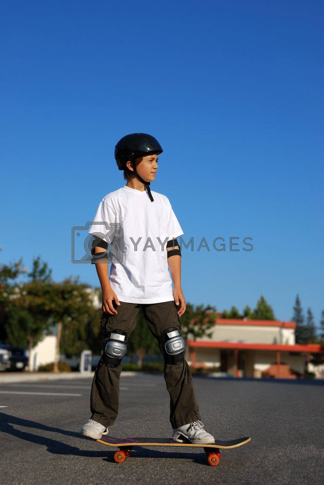 boy standing on a skateboard in an afternoon sun with blue sky in the background
