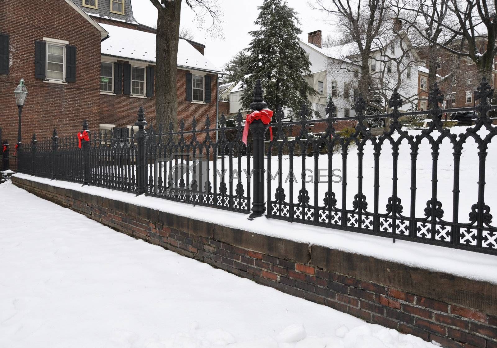 fancy blank iron fence in winter with red bows and snow