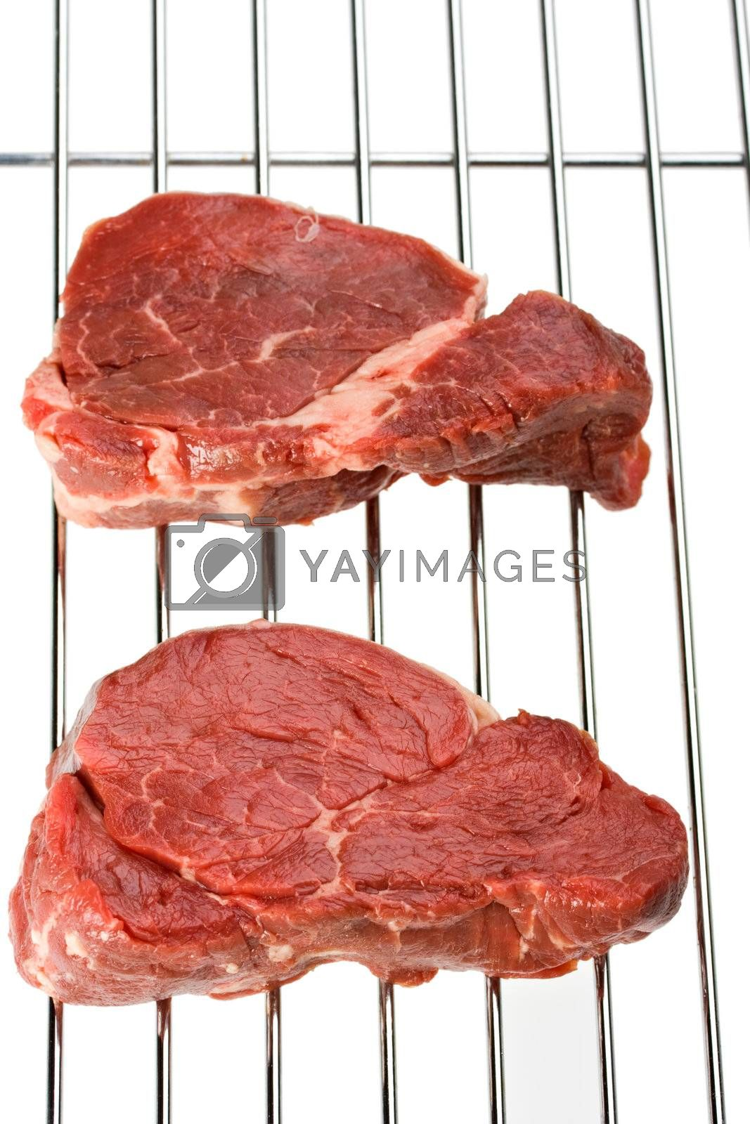 raw steak on a grill isolated on white