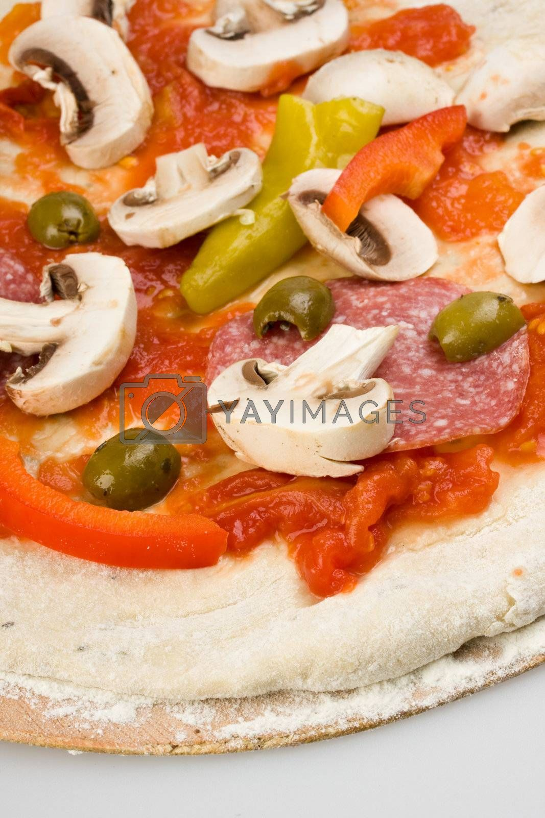 unbaked pizza prepared to bake on a wooden board