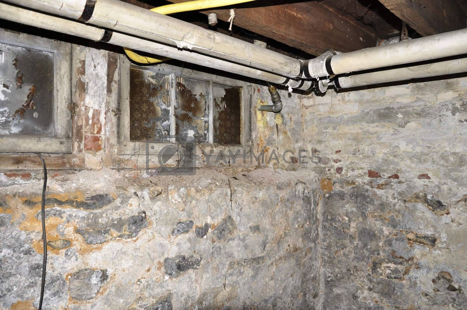 interior plumbing pipes by an old stone basement wall