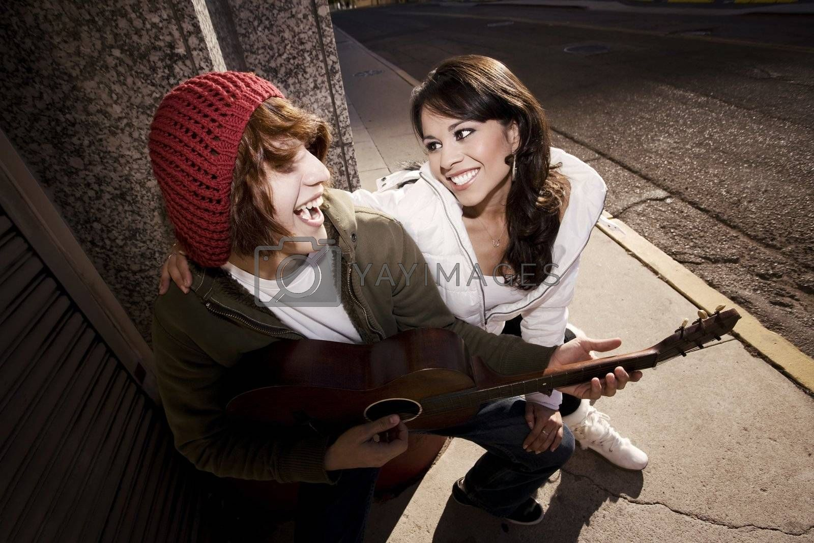 Hispanic musician and Latina Girlfriend downtown at sundown