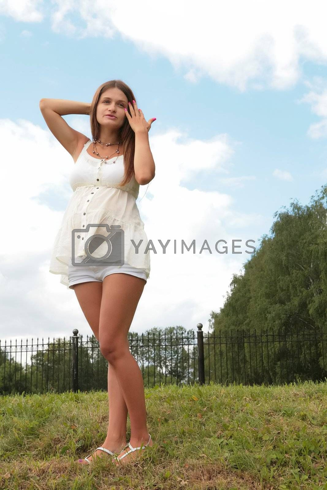 vertical summer portrait of the expectant mother in white cloth stand on herb under blue sky