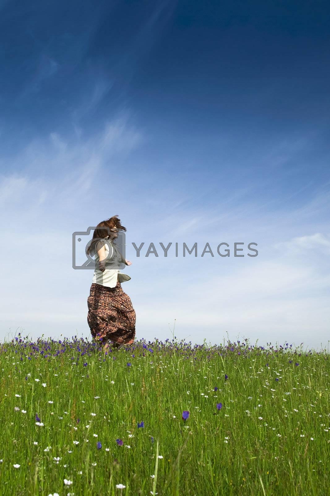 Young woman dancing on a beautiful green meadow