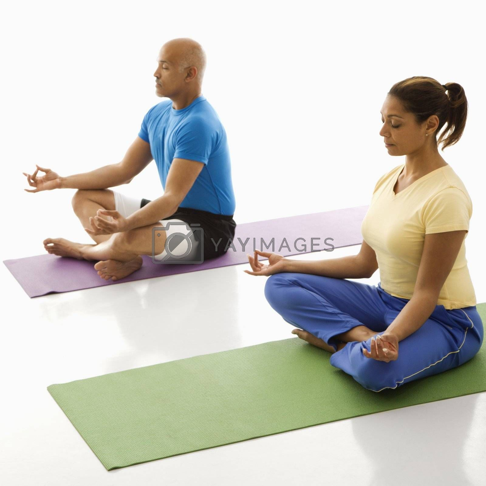 Mid adult multiethnic man and woman sitting in lotus position on exercise mats with eyes closed and legs crossed.