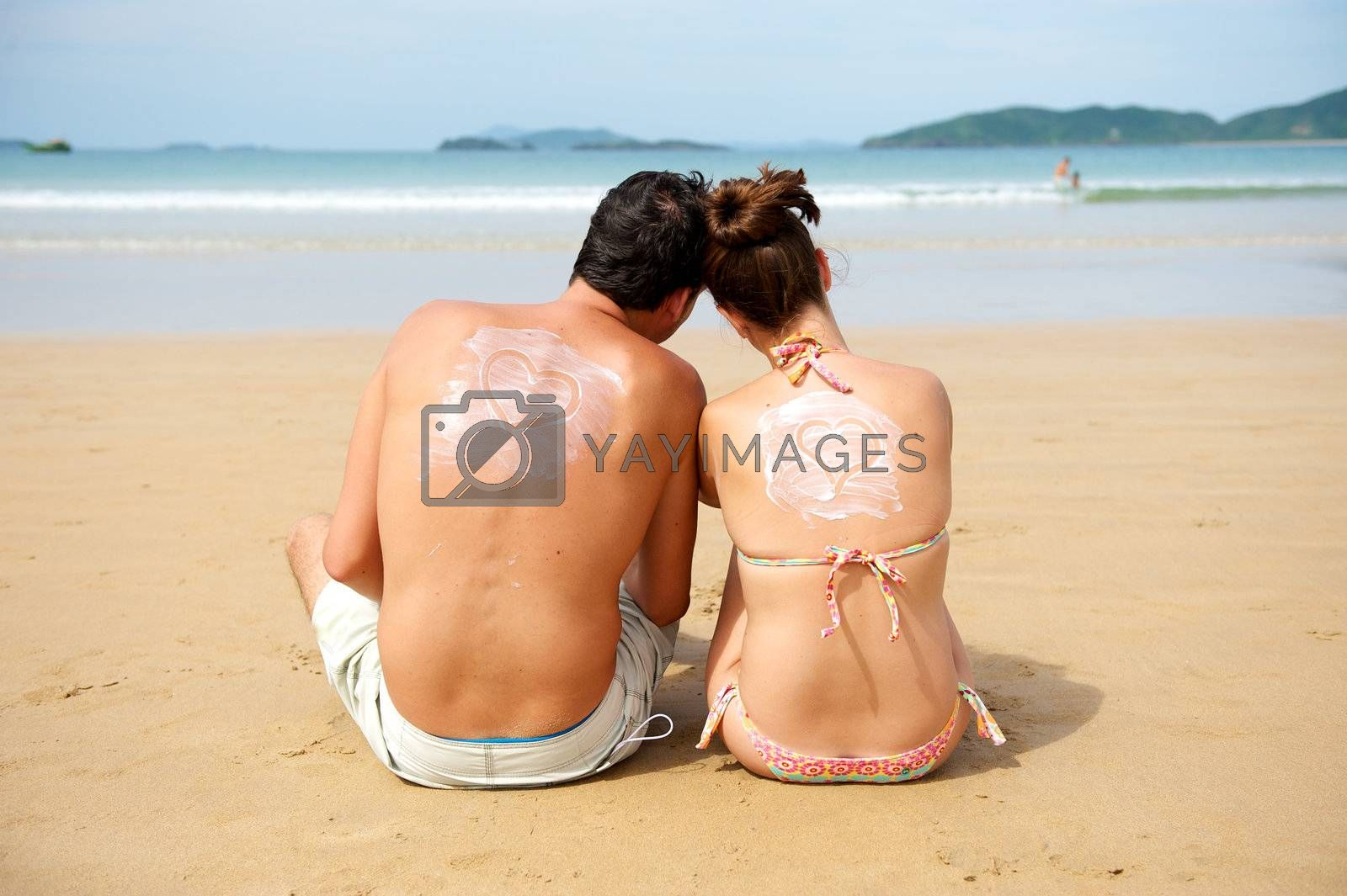 Young couple enjoying the beach with an heart draw on their backs
