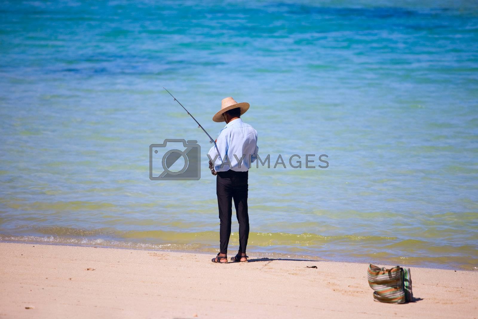Fisherman fishing from beach. Lifestyle scene from Mauritius
