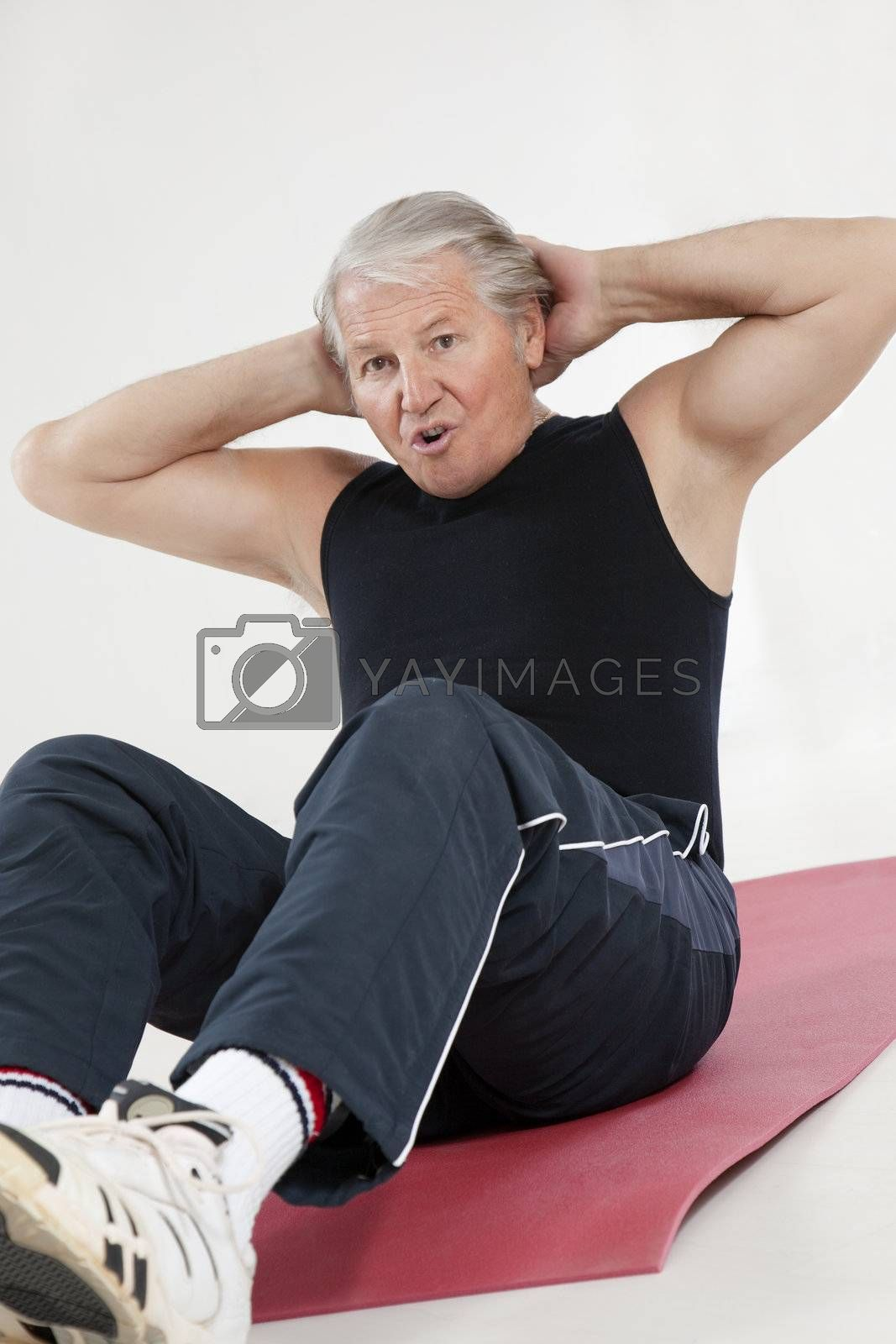 senior man doing abs exercise in health club