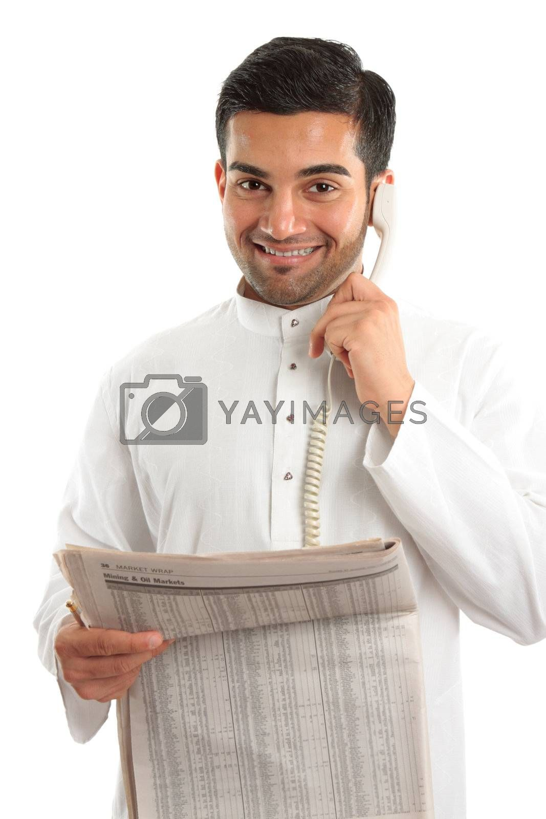 An ethnic italian / arab mixed race businessmanwearing traditional middle eastern clothing.  He is on the telephone and holding a newspaper at finance section.  White background.