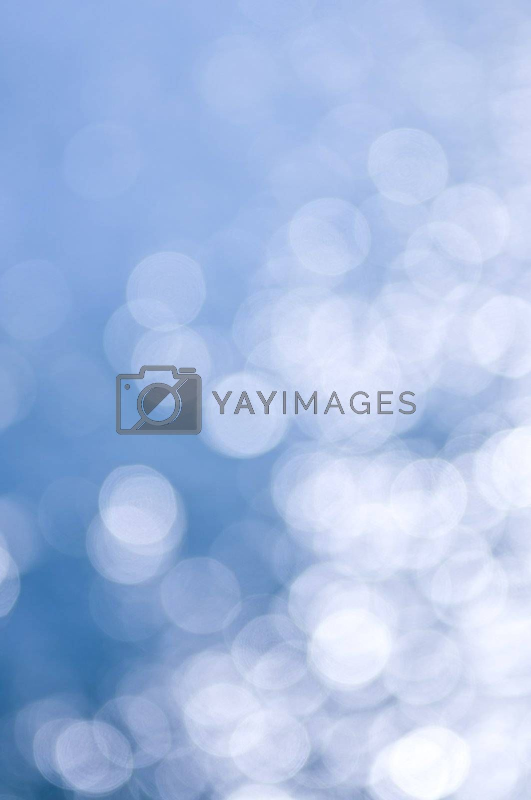 Out of focus bokeh background of blue water with sun reflections. Can be used as Christmas or winter backdrop.