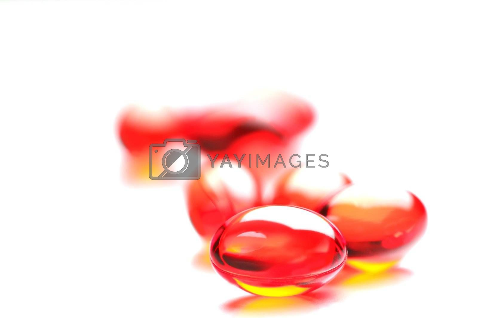 closeup bright red pills on white background