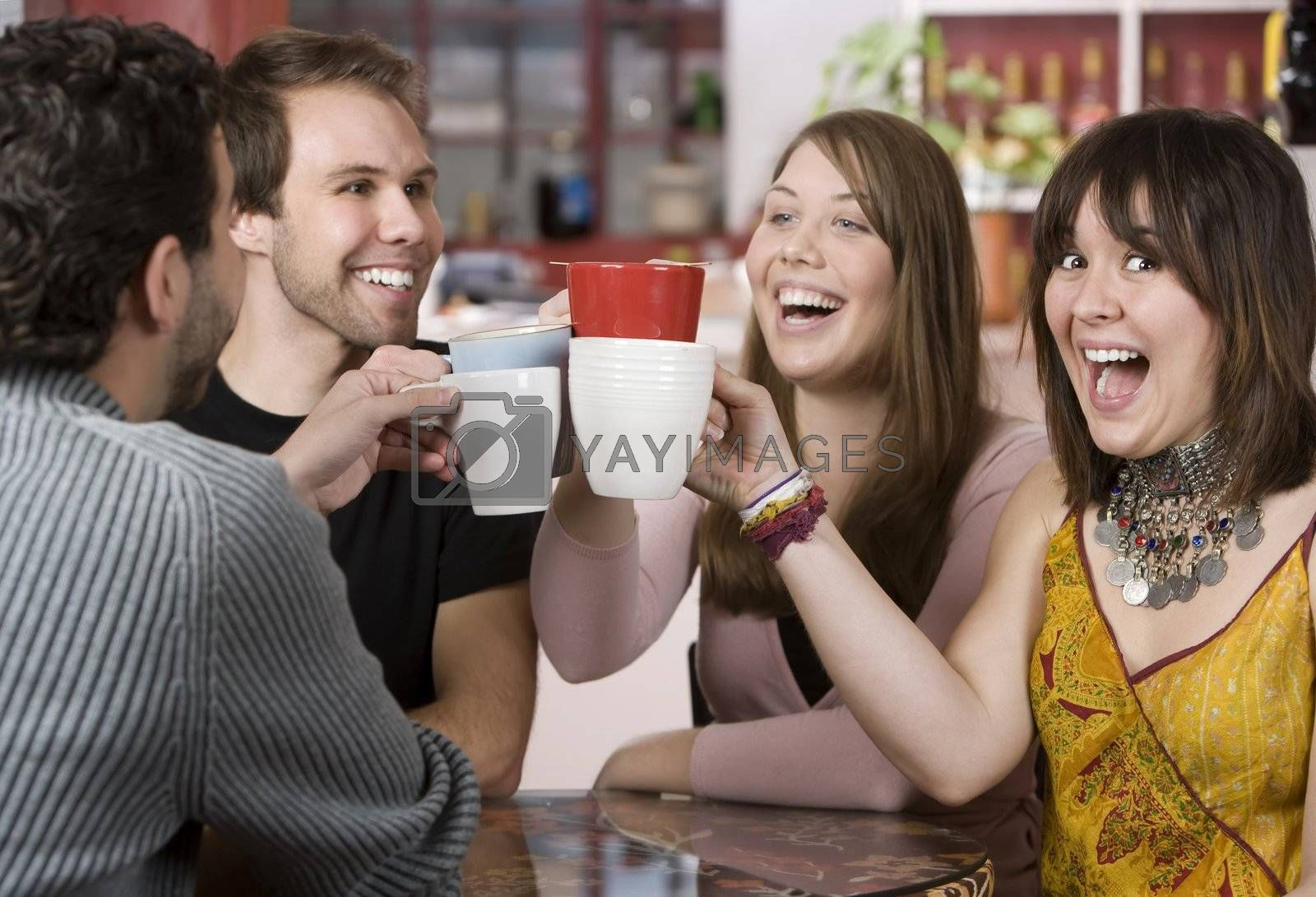 Royalty free image of Young Friends Toasting with Coffee Cups by Creatista